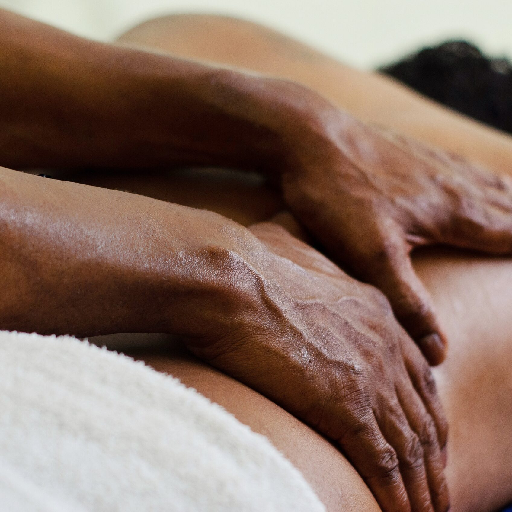 Dark-skinned hands give a relaxing massage to man. dark skin lying on the stretcher